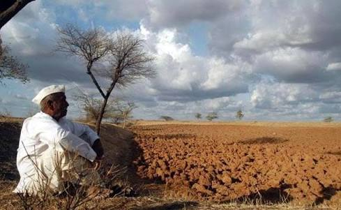 A farmer sitting in despair in front of barren land- Indian economy today